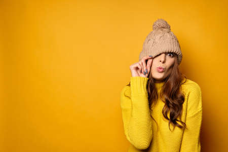 A brunette in a yellow sweater stands on a yellow background, pulling a hat over one eye and stretching out her lips in a kiss Фото со стока