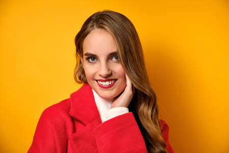 A girl with red lips in a coat is standing with a smile on a yellow background