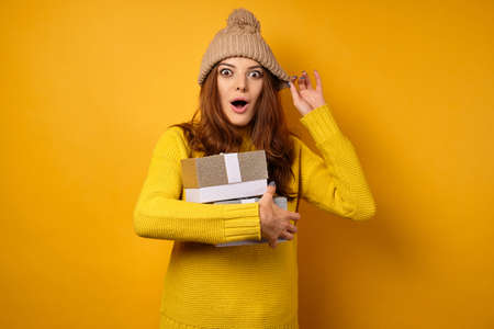 A brunette in a yellow sweater and hat stands in surprise opening her mouth and eyes, clutching gift boxes to herself