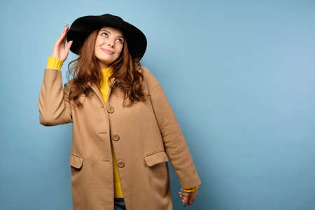 The brunette stands on a blue background in a yellow sweater, trench coat and black hat, looks cute at the top.