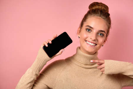 A girl with clean skin and a high bun joyfully points to the smartphone with her finger and looks at the frame. Фото со стока