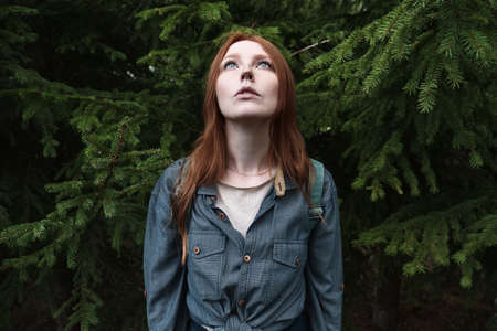 A redhead girl with blue eyes in a denim shirt stands straight and looks up holding her head against the background of fir trees