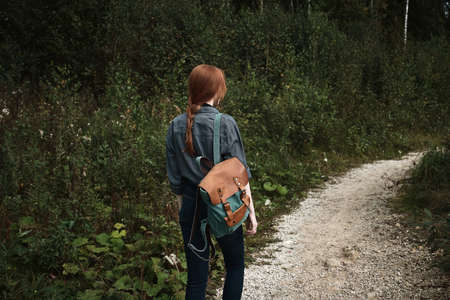 A red-haired girl is walking in the forest along the road with a backpack, a frame from the back from the side. Фото со стока