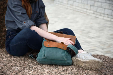 A close shot of a girl sitting on a stone with a backpack in her hands.