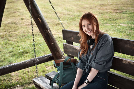 Redhead girl in a denim shirt sits with a backpack on a wooden swing bench and smiles into the frame.