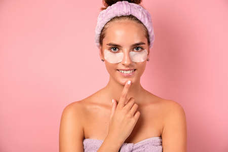 A girl with clean skin stands on a pink background in a towel with patches under her eyes and smiles.