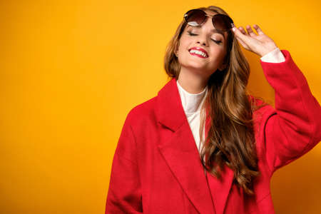 A beautiful girl with red lipstick in a coat with her head back and smiling with her eyes closed, raising sunglasses