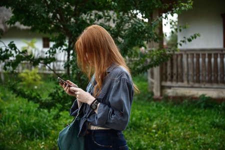 A red-haired girl in a denim shirt stands in profile with head bowed and looks at the phone against the backdrop of a green yard