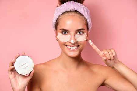 A girl with clean skin stands on a pink background with patches under her eyes, cream on her nose and shows a finger at the camera Фото со стока
