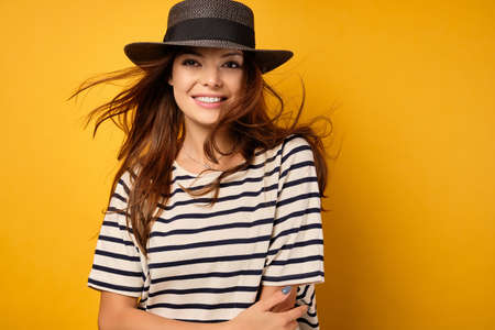 Lovely brunette in a striped T-shirt and wicker hat smiles hugging herself, hair fluttering in the wind, on a yellow background Фото со стока
