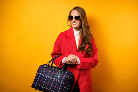 A girl with red lips in a coat and sunglasses stands on a yellow background with a travel bag and smiles Фото со стока