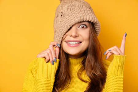 A brunette in a yellow sweater stands on a yellow background, pulling a hat over one eye and smiles, points a finger at the top.