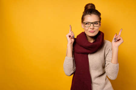 A girl in a scarf and glasses with a high beam points her fingers up with a sly face twinkle on a yellow background.