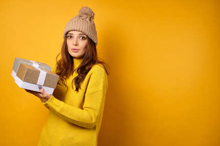 A brunette in a yellow sweater and hat stands half a turn on a yellow background, looks confusedly holding gift boxes in hands
