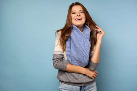 A brunette in a sweater and a blue scarf stands on a blue background, and looks into the frame laughing.