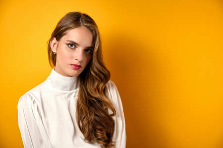 Beautiful girl with clean skin, curls and red lipstick stands on a yellow background. Фото со стока