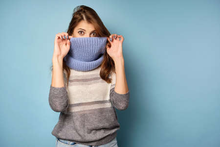 A brunette in a sweater stands on a blue background and covers her face with a scarf to her eyes, looks into the frame.
