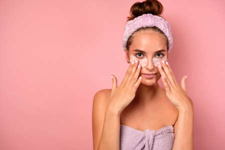 A girl with clean skin stands on a pink background in a towel and with her fingers straightens patches under her eyes.