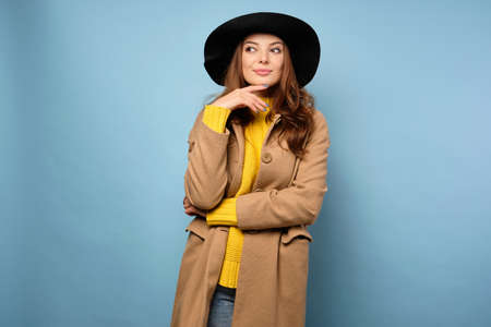 The brunette stands on a blue background in a yellow sweater, trench coat and black hat, looks away, raising an eyebrow.