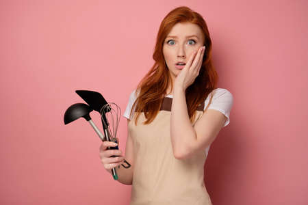 A red-haired girl in a apron on a pink background, holds kitchen appliances in hand and with surprise, presses hand to face
