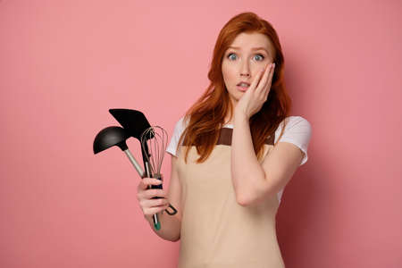 A red-haired girl in an apron stands with kitchen appliances and looks in horror at the frame with palm pressed to face Stock Photo