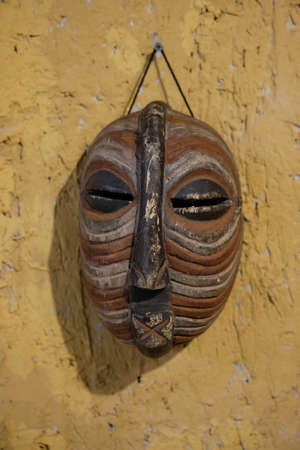 African wooden mask hanging on a stone yellow wall.