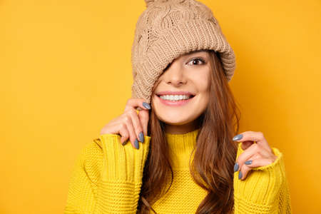 A brunette in a yellow sweater is standing on a yellow background, smiling and pulling her hat over half of her face. Stock Photo