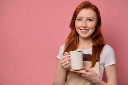 The red-haired girl in an apron stands on a pink background with a white cup in her hand and smiles broadly