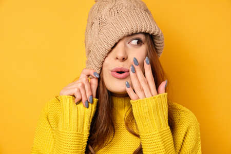 A brunette in a yellow sweater is standing on a yellow background, pulling the cap over half of face and covering mouth looks away