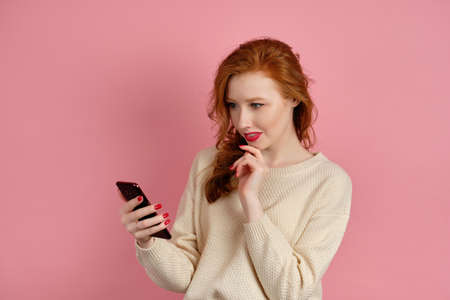 A red-haired girl with red lipstick is half a turn on a pink background and looks doubtfully at the phone