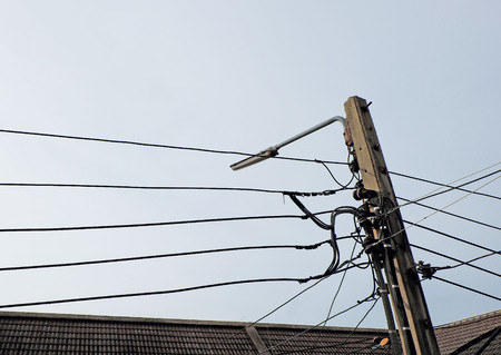 lamp post: Lamp post with many cords among the light blue sky Stock Photo
