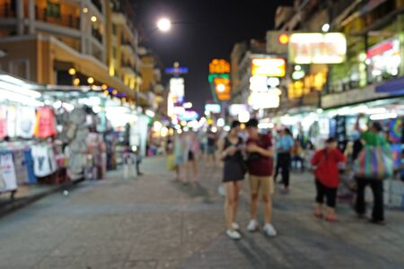 wanderers: Travelers stands and downs their head to watch a map among the people at night market in blur mode Stock Photo