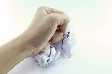 wastrel: one fist smash on the wrinkled crumpled marketing report paper balls Stock Photo