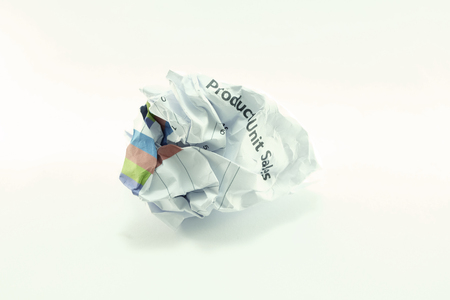 wastrel: wrinkled crumpled marketing report paper ball with bright wallpaper Stock Photo