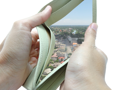 managing money: The wallet is opened by both hand in white background and found many buildings and houses Stock Photo