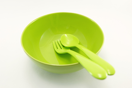 green plastic spoon and fork are placed in a green bowl with bright background Stock Photo