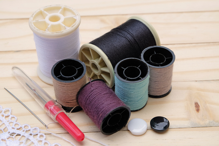 sooth: Embroidery Equipmentneedle,thread,buttons and lace with wood floor