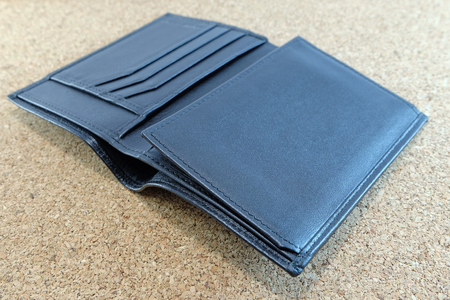 Black wallet is rolled out on plywood floor
