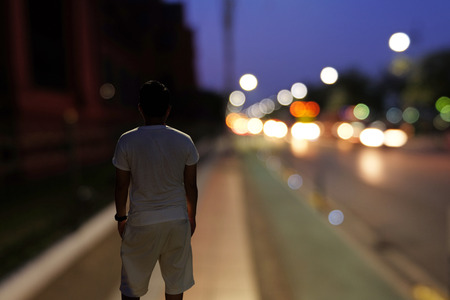 nightscape: Backside of Man who stands on street corridor and looks forward to the road and some vehicles at night in blur mode