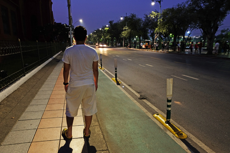 pointless: Backside of Man who stands on street corridor and looks forward to the road and some vehicles at night Stock Photo
