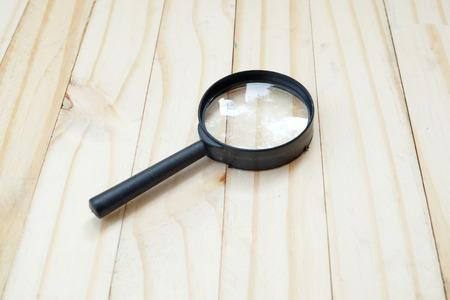 emit: black plastic Magnifier on wood floor Stock Photo