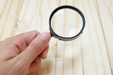 black plastic Magnifier with handle held by hand on wood floor