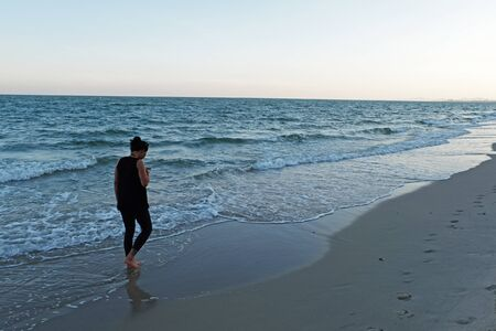 spiritless: cellphone touch screen is touched by lady who wears all black clothes with bare feet and walk along the beach in almost sunset and dark tone
