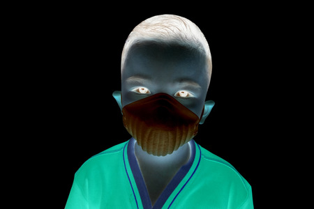 The boy Wears a white dust mask in invert mode with black background Stock Photo