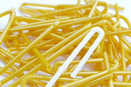 fold-able joint of white milk plastic straw on milk yellow plastic straws pile on white ground Selective focus Stock Photo