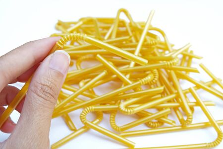 fold able joint of yellow straw which is held by hand on yellow straws pile and white ground Selective focus
