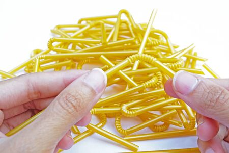 fold-able joint of yellow straw which is held by two hands on yellow straws pile and white ground Selective focus