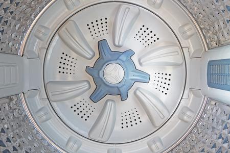 blue spinning agitator selective focus inside a washing machine