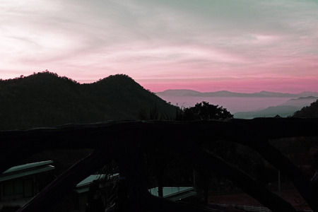 wanderers: some mountains,trees and gradient light and deep pink sky while before sunrise silhouette mode Stock Photo