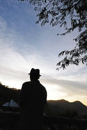wanderers: a man Selected focus who wears a hat with some mountains,tree and gradient light orange-blue sky while before sunrise silhouette mode